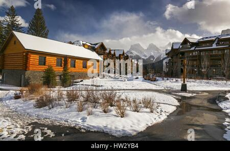 Spring Creek Alpine Village in Canmore, Alberta and distant snowy Three Sisters Rocky Mountain Tops near Banff National - Stock Photo