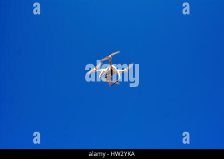 Aircraft type Dron photographed from the ground in flight and shooting events below it - Stock Photo