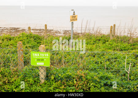 HUNSTANTON, ENGLAND - MARCH 10: The Samaritans sign 'talk to us, if things are getting to you' next to crumbling - Stock Photo