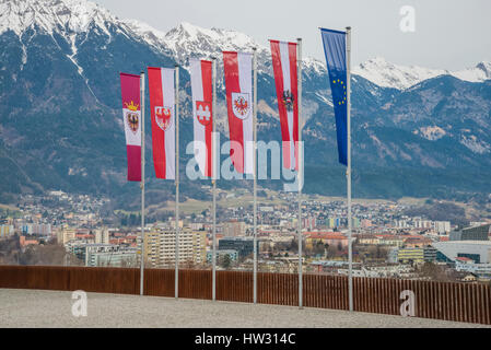 Austrian provincial flags and flag of the European Union at Bergisel above the city of Innsbruck and the mountains - Stock Photo