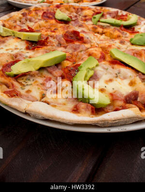 Pizza on dark wooden table top with fresh ingredients - Stock Photo