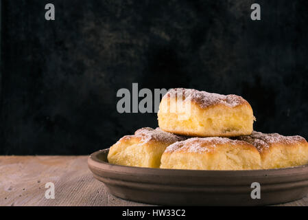 Horizontal photo of traditional rustic sweet bun cakes with cream cheese inside and powder sugar on surface. Food - Stock Photo