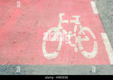 Bicycle symbol in white on a pink asphalt. Bicycle path - bicycle way is a good sign for safe the cyclists. - Stock Photo