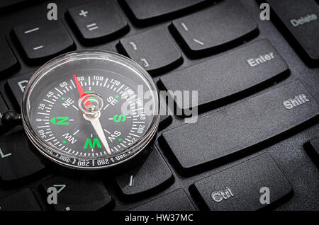 Black computer keyboard and compass showing internet navigation concept. - Stock Photo