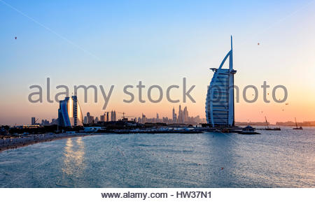 Jumeirah Beach Hotel and the  iconic Burj Al Arab Hotel with Hot air Balloons passing behind it at sunset time, - Stock Photo