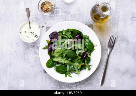 Healthy food, green salad with mixed leaves of arugula, mesclun, spinach on light stone background. Top view - Stock Photo