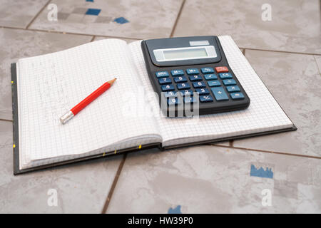 notebook in mathematics with handwriten exercise and a pencil and black calculator on ceramic surface desk - Stock Photo