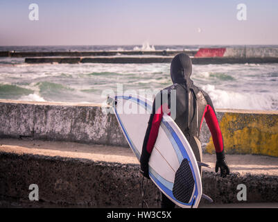 Surfer on the pier walks  into water wearing a wetsuit in winter. Cold surfing. Wave splash. waterproof suit - Stock Photo