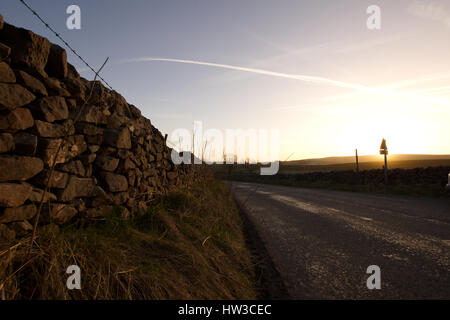 Stone wall and rural ,country sideroad during sunset in Peak District National Park,Derbyshire,United Kingdom. - Stock Photo