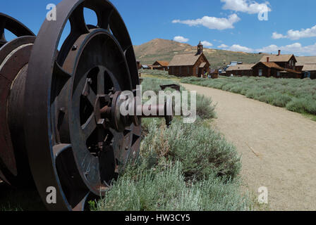A large piece of mining equipment is on the left side of the frame, with a church and other buildings at Bodie, - Stock Photo