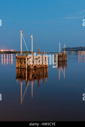 Two old, disused, wooden jetty's, reflected in the very calm waters of Cardiff Bay, Wales, UK, at night time