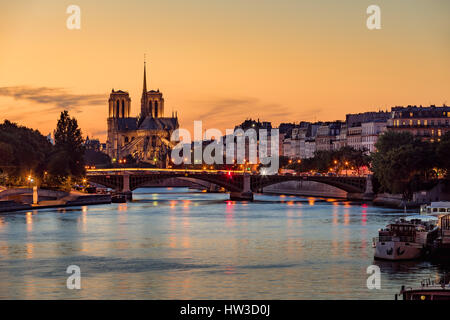 Notre Dame de Paris Cathedral, Ile Saint Louis and the Seine River at sunset. Summer evening with the Sully Bridge - Stock Photo