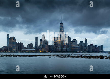 New York City Financial District skyline in early morning from across the Hudson River. Low storm clouds over the - Stock Photo