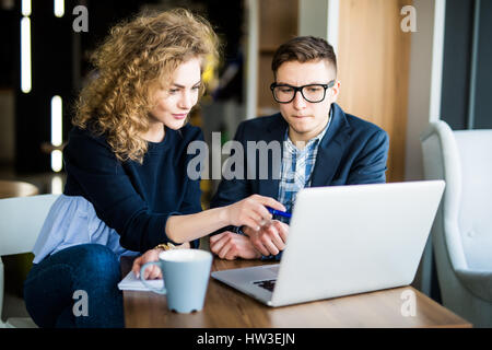 Group of two coworkers working over laptop discuss in a modern office in the background - Stock Photo