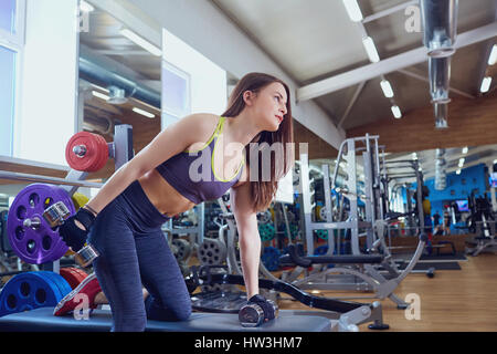Young sporty girl with dumbbells in hands doing exercises in spo - Stock Photo