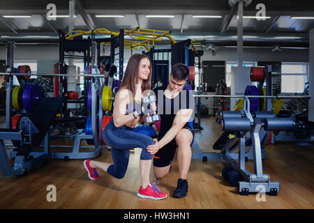 Personal trainer instructor helps to do exercises for  sports gi - Stock Photo