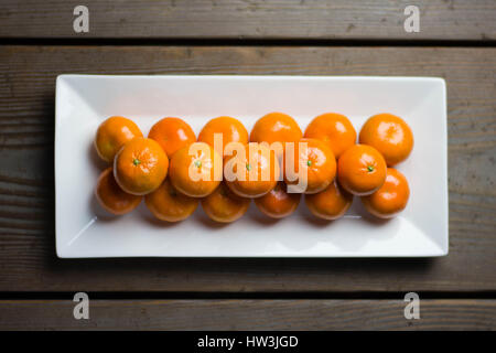 Tangerines symmetrically lined up on white plate with rustic table in the background. - Stock Photo