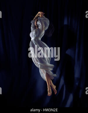 Beautiful young woman dancer in a flowy dress spinning gracefully in the air, spotlight with a black blue stage - Stock Photo