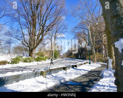 Woman crossing cleared road in snowy Central Park. Late winter 2017. New York, New York, USA - Stock Photo