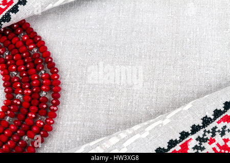 Slavic culture: traditional female beads of garnet with inclusions rock crystal on natural linen (cloth) background - Stock Photo