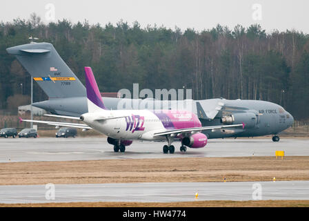 Gdansk, Poland. 17th Mar, 2017. Wizzair aircraft Airbus A320-200 and United States Air Force large military transport - Stock Photo