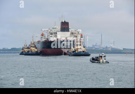 Super tanker Stavanger Prince being assisted into Milford Haven by three tugs and being followed by the Police rib. - Stock Photo