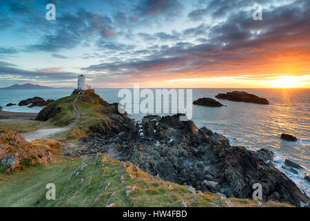 Stunning sunset over the Twr Mawr lighthouse on Ynys Llanddwyn on the Anglesey coast in north Wales - Stock Photo