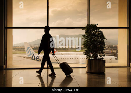 Tourist with luggage at Malaga airport. Costa del Sol, Malaga. Andalusia southern Spain. Europe - Stock Photo