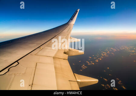 View of airplane wing through window - Stock Photo