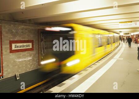 Berlin subway (U-Bahn):Yellow wagon in motion at Alexanderplatz station - Stock Photo