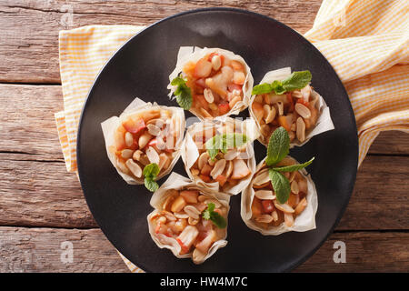 Homemade Mini Phyllo Cupswith apples and peanuts closeup on a plate. Horizontal view from above - Stock Photo