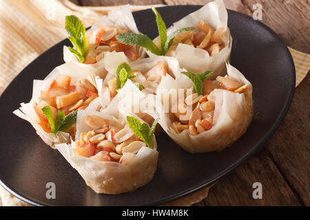 Phyllo dough cups with apples and peanuts closeup on a plate. horizontal - Stock Photo