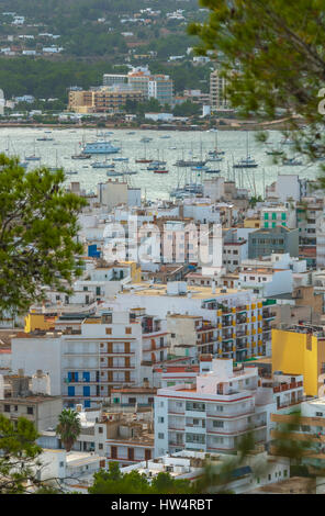 View through naturally framing trees, from hillside of nearby town: San Antonio Sant Antoni de Portmany in the Balearic - Stock Photo