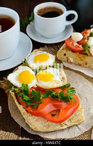 Bruschetta with quail egg, bell pepper and herbs. Light breakfast. - Stock Photo