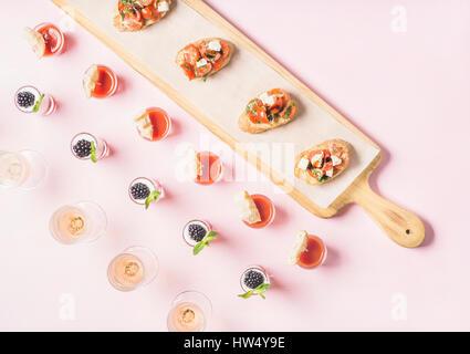Snacks, brushetta sandwiches, gazpacho shots, desserts over pastel pink background - Stock Photo