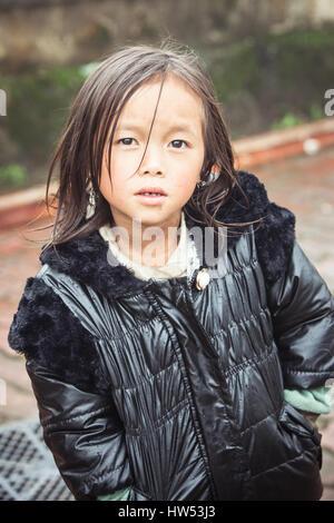 Sapa, Vietnam - May 6, 2014: Portrait of little vietnamese girl in the rainy weather on the street of Sapa village, - Stock Photo