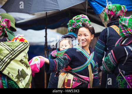 Sapa, Lao Cai, Vietnam - 6 May 2014: Portrait of tribal Hmong woman with baby in national clothes on the local market, - Stock Photo