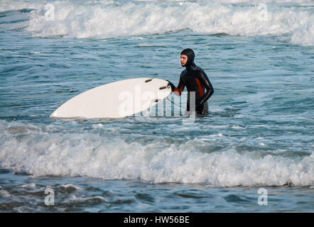 Surfer walks from water with surfboard wearing a waterproof suit. - Stock Photo