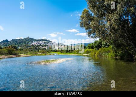 View from the river of a mountain village with a castle on top. Jimena de la Frontera, Cádiz, Spain. - Stock Photo