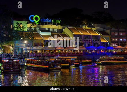 Clarke Quay outdoor precinct at night with busy cafes and restaurants along the riverside, Clarke Quay, Singapore - Stock Photo