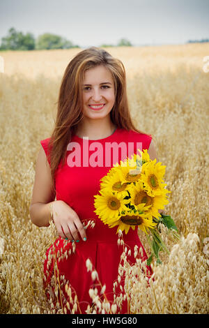 Portrait of beautiful brunette girl with long hair wearing in red dress standing among pikelets in field. Young - Stock Photo