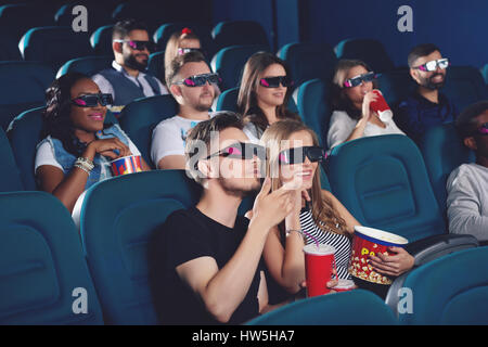 Boyfriend and gifriend watching  movie in cinema and emotionaly gesturing. - Stock Photo