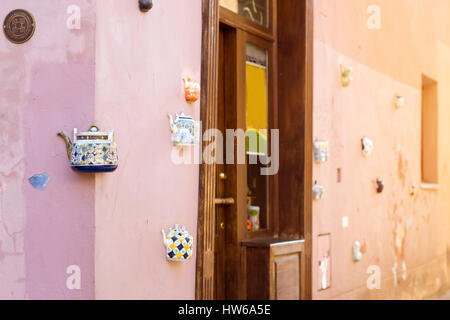 Vilnius, Lithuania - August 8, 2012: Vintage ceramic teapots embedded in facade corner of historic building on main - Stock Photo