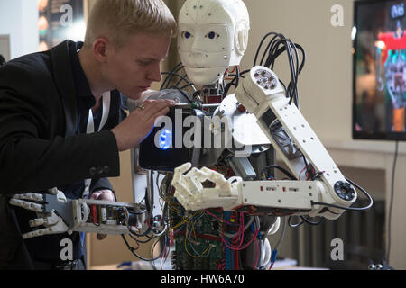 A young scientist testing an anthropoid robot at the Robostation, at Moscow's VDNKh Exhibition Center in Russia - Stock Photo