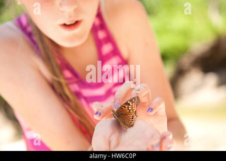 Girl with butterfly in hand - Stock Photo