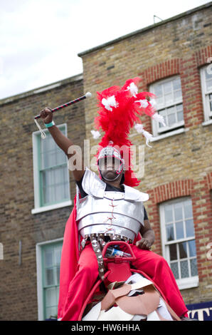 Carnival in Hackney a black man holds a baton like a Roman soldier wearing a costume of body armour and a flaming - Stock Photo