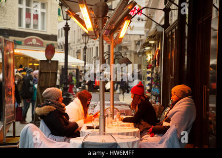 Young people on a terrace of a bar at dusk. Cold winter. Budapest Hungary, Southeast Europe - Stock Photo