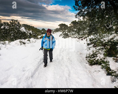Hiker on snow covered footpath, Sierra de Mijas. Malaga province. Costa del Sol, Andalusia Southern Spain.Europe - Stock Photo