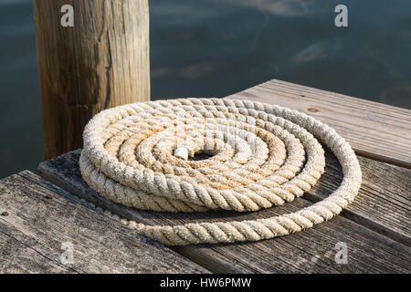 A close up shot of an old coiled nautical rope on a wooden pier next to the water in Mystic, Connecticut - Stock Photo