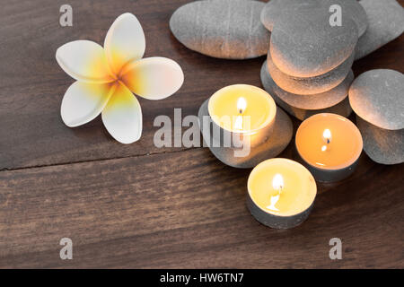 spa composition with candles pebble stones and flowers on wooden table - Stock Photo